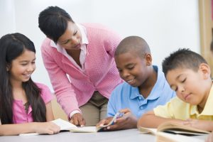 Teacher helping elementary school reading group